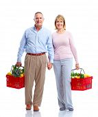 Grocery. Happy senior couple with a shopping basket .