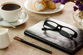 Black Leather Notepad, Black-rimmed Spectacles, Pen With Brown Cap, White Coffee Cup, Rolls With Cre poster