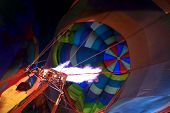 Man Filling The Orange Balloon With Hot Air. View Of The Flame Inside Of A Hot Air Balloon Being Inf poster