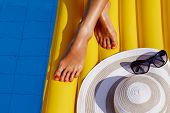 Portrait Of Beautiful Tanned Woman Relaxing In Bikini In Swimming Pool. Legs Close Up. Gel Polish Re poster
