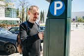 A Man Pays For Parking Using A Special Machine To Pay In Lisbon In Portugal. poster