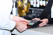 Credit Card Payment And Electronic Bank Concept. Cashiers Hand Holds Credit Card Terminal On Defocus poster