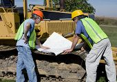 image of dozer  - two construction contractors looking at drawings on a bull dozer - JPG