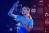 Fascination Hologram. Smart Progressive Schoolgirl Standing With A Futuristic Gadget And Looking Imp poster