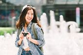 Young Beautiful Asian Backpack Traveler Woman Using Digital Compact Camera And Smile, Looking At Cop poster