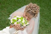 The Bride With A Bouquet On The Background Of Green Grass.