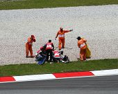 SEPANG, MALAYSIA - OCTOBER 23: Track medical staff assist 125cc rider Marcel Schrotter after he crashed on race day of the Malaysian Motorcycle GP 2011 on October 23, 2011 at Sepang, Malaysia.