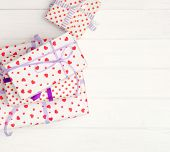 Lovely giftboxes on white wooden table wrapped in heart pattern paper with purple ribbon. Happy Vale poster