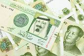A Close Up Image Of A One Riyal Bank Note From Saudi Arabia On A Background Of Chinese One Yuan Bank poster