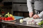 Young Chef Cutting Beet On A White Cutting Board Closeup. Cooking In A Restaurant Kitchen poster