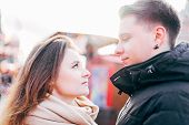 Portrait Of Cheerful Young Couple Looking At Each Other On The Street In Winter. With Sunbeams In Be poster