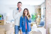 Young beautiful couple standing at new home around cardboard boxes asking to be quiet with finger on poster
