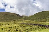 Pastures And Volcanic Rock Walls With Clouds In The Distance On Pico Island In The Azores, Portugal. poster