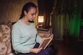 Young Woman In Sweater Sits On Sofa And Reads Book In Shadows. Adult Lady Enjoys A Reading Her Favor poster