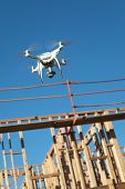 Drone Quadcopter Flying and Inspecting Wood Framing at Construction Site. poster