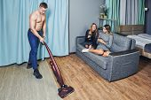 A Muscular Young White Man Is Vacuuming The Floor Of A University Dormitory Using A Cordless Vacuum  poster