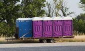 picture of porta-potties  - A set of blue and purple porta potty toilets on a trailer ready to be shipped to an event - JPG