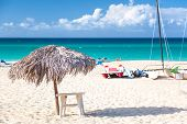 Straw Umbrella On Empty Seaside Beach With A Sailboat In Varadero, Cuba. Relaxation, Vacation Idylli poster