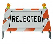 A road blockade or barrier with the word Rejected, communicated a negative message of denial, refusa