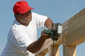 picture of 2x4  - Worker man sanding wood frame on anew construction - JPG