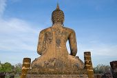 View From The Back Of Ancient Sculpture Of A Sitting Buddha Against  Blue Sky. Sukhothai, Thailand poster
