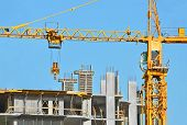 stock photo of structural engineering  - Building crane and building under construction against blue sky - JPG
