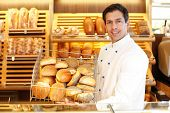 foto of confectioners  - Baker in a bakery presents a breadbasket to customer - JPG
