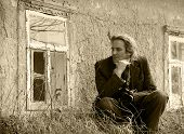 Sad Middle-aged Man Sitting In Front Of An Abandoned House. Vintage