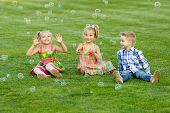 Portrait Of Three Friends With Soap Bubbles