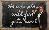 Teacher Showing He Who Plays With Fire Gets Burnt On Blackboard