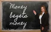Teacher Showing Money Begets Money On Blackboard