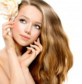 Beauty Girl. Beautiful Model with Rose Flower Touching her Face. Healthy Long Hair and Clear Skin. Y