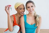 Portrait of two cheerful female friends with house keys sitting on the floor