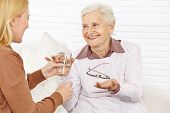 Smiling senior citizen woman taking medical pill with a cup of water