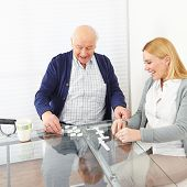 Woman playing domino with senior man in a retirement home