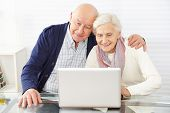 Senior couple using ecommerce in internet with laptop computer