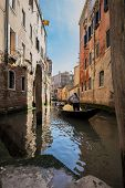 stock photo of gondolier  - Gondolier guiding tourists through a Venetian canal - JPG
