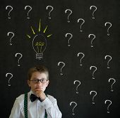 Thinking boy dressed up as business man with questions and ideas on blackboard background