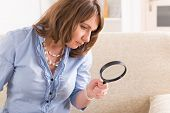 Beautiful woman holding loupe or magnifying glass