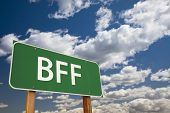 BFF, Texting Abbreviation for Best Friends Forever, Green Road Sign with Dramatic Sky and Clouds.
