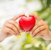 health and charity concept - close up of woman hands holding heart
