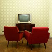 Vintage room with two old fashioned armchairs and retro tv over obsolete wallpaper