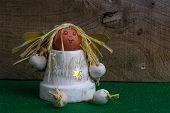 foto of elm  - Christmas decoration homemade angel from ceramic pot on green fabric and rustic Elm wood background  - JPG