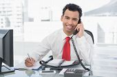 Portrait of a smiling businessman writing notes while using land line phone at a bright office