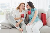 stock photo of slumber party  - Two happy young female friends with coffee cups conversing in the living room at home - JPG