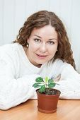 Smiling young woman sitting with green plant in flowerpot