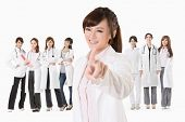 Asian doctor woman stand in front of her team and point at you, closeup portrait on white background