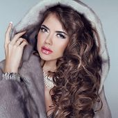 Beautiful Brunette Girl Wearing In Mink Fur Coat With Long Hair Styling Isolated On Grey Background.