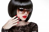 Fashion Portrait Of A Beautiful Brunette Woman With Shot Hairstyle With Red Sunglasses. Red Lips. Ma
