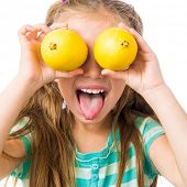 little girl with two lemons shows tongue isolated on white background